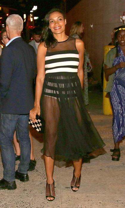 Fresh from promoting 'Top Five' at TIFF, Rosario Dawson was spotted at Opening Ceremony's show at New York Fashion Week in a gauzy, sheer dress with a striped leotard bodice. © Getty