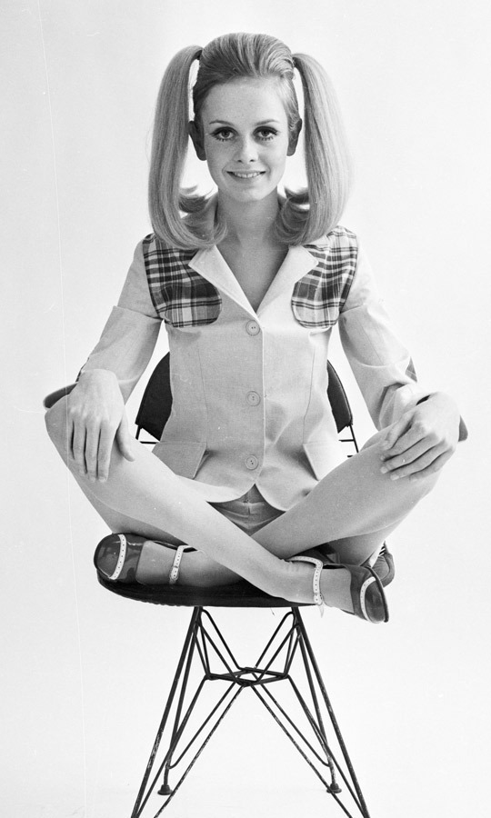 1967: 'Daily Express' continued to feature Twiggy prominently among its pages in 1967, when she sat for this stunning shoot wearing pigtails and a tartan-accented suit. (Image: Express Newspapers/Getty Images)