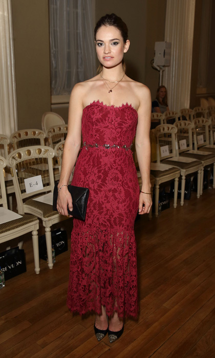 Actress Lily James arrived at the Marchesa show during London Fashion Week in a frayed, crimson-lace gown by Marchesa Notte with a jeweled belt, envelope clutch and cap-toe pumps.