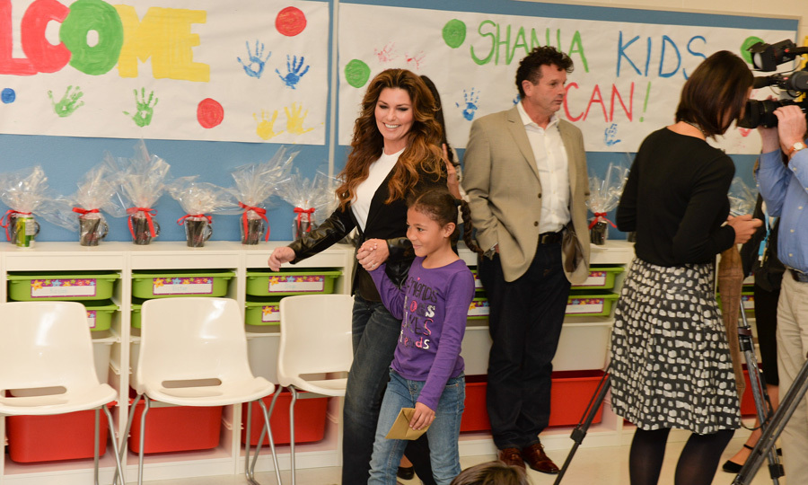 Shania Twain finds a welcome escort in one of the children at Sir Winston Churchill Public School.