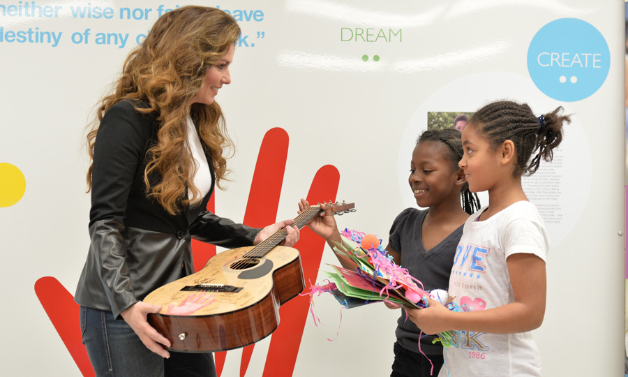 The Canadian songstress shows two adorable little girls bearing handmade gifts one of the instruments of her success (the other, of course, being her powerful voice!)