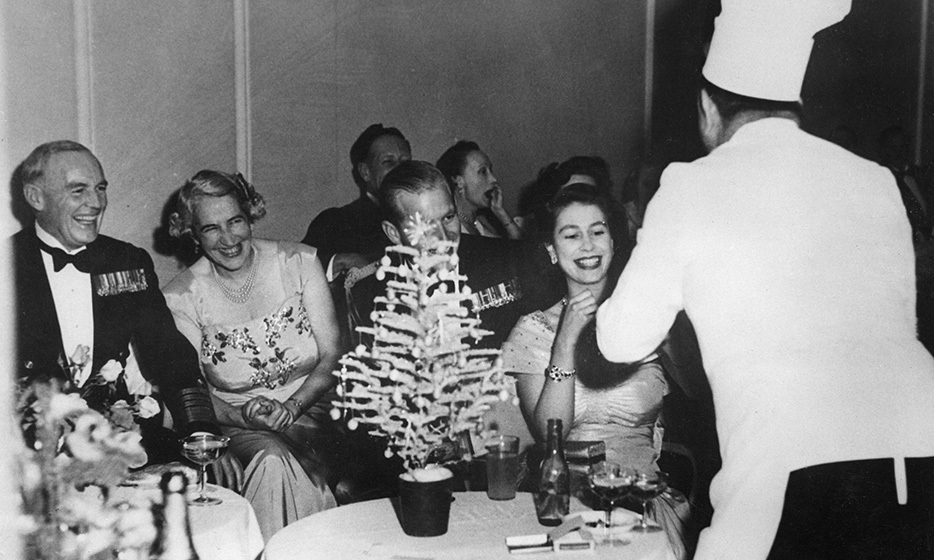 In 1951, the Queen attended a dance at the Hotel Phoenicia with Prince Philip by her side, where she bought a hot dog from Captain Ben Fisher, here dressed up as a chef. Photo: © Illustrated London News Ltd/Mary Evans