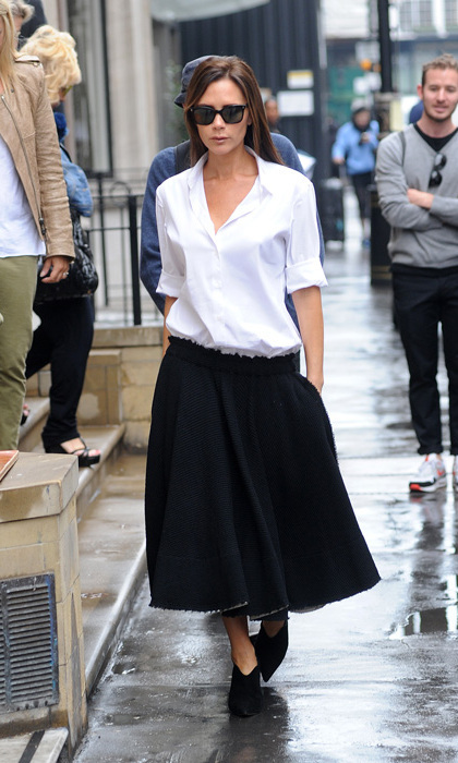 Victoria Beckham made a stylish stop to her eponymous London boutique in an oversized button-down shirt, low-slung full skirt and ankle booties.