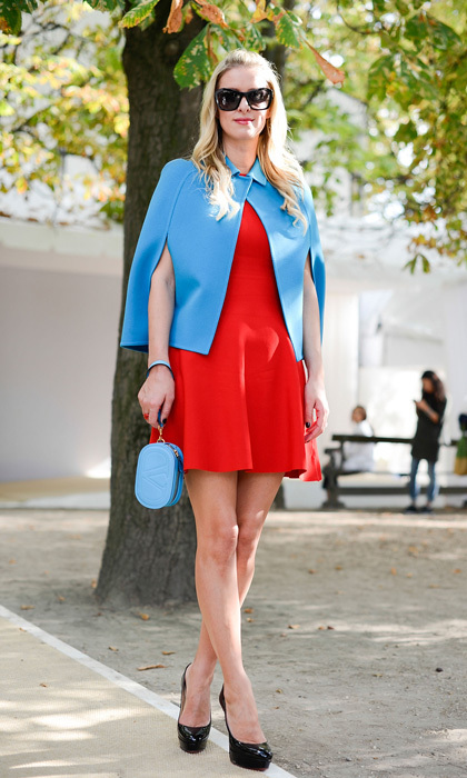 Nicky Hilton was superhero chic in a cerulean cape and red skater dress at the Valentino fashion show during Paris Fashion Week. The socialite accessorized with oversized sunnies, patent leather heels and a sky-blue Valentino wristlet.