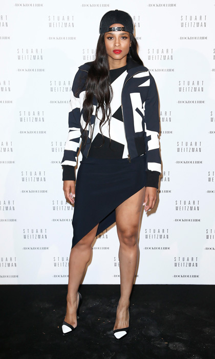 Ciara struck a pose at a Stuart Weitzman event in a head-to-toe look by Anthony Vaccarello, featuring an asymmetrical dress and printed bomber by the designer. The singer topped off her look with a black snapback hat and cap-toe heels.