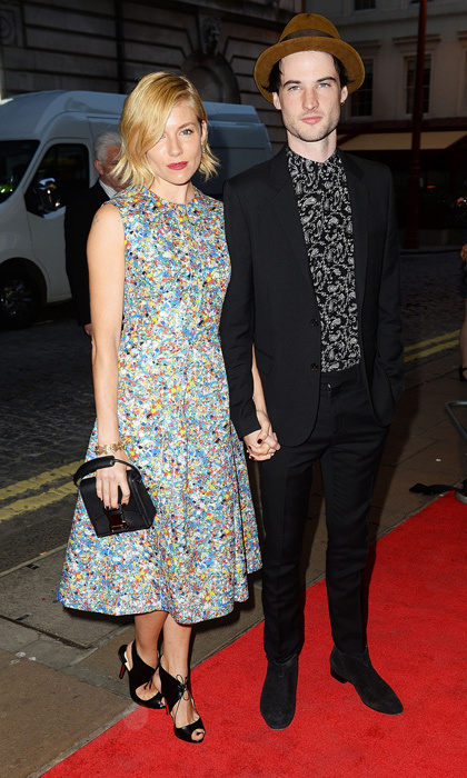 Sienna Miller walked the 'Effie Gray' red carpet hand-in-hand with husband Tom Sturridge in a printed tea dress by Roksanda, a Christopher Kane clutch and lace-up Nicholas Kirkwood sandals.